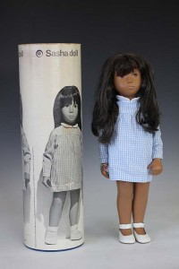 A Trendon Ltd Sasha Doll dark haired doll dressed in a blue and white gingham patterned dress