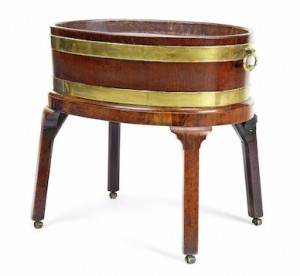 A George III mahogany and brass mounted wine cooler of oval form, the stand comprising four legs terminating in brass castors Sold at Bonhams, Knightsbridge for £1,187 inc. premium, Feb 2016