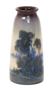 A Rookwood Pottery vase, dated 1911, model no.1658E tapering cylindrical form, painted with trees on a lake side landscape in vellum colours impressed factory marks, 20cm. high Sold for £750, October 2015 at Wolley and Wallis