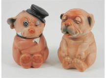 "Two Bonzo bisque jars with removable heads, German 1920's, the seated Bonzo's, painted in orange and with moulded and painted features, the string pull jar with hole to mouth, the other winking with moulded black top hat and moulded suit collar, tallest 6"" (15cm) tall"