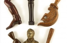 A rare early 19th century West Indies carved horn pipe tamper, with a head finial having braided hair and a pewter collar, replaced base, 3¼in (8.2cm) high, an 18th century boxwood squirrel pipe tamper, 3¼in (8.2cm) high, an 18th century boxwood pipe tamper with chip carved geometric decoration, a 19th century treen boot and leg pipe tamper, a 19th century treen shoe pipe tamper and a brass bust of the Duke of Wellington pipe tamper.